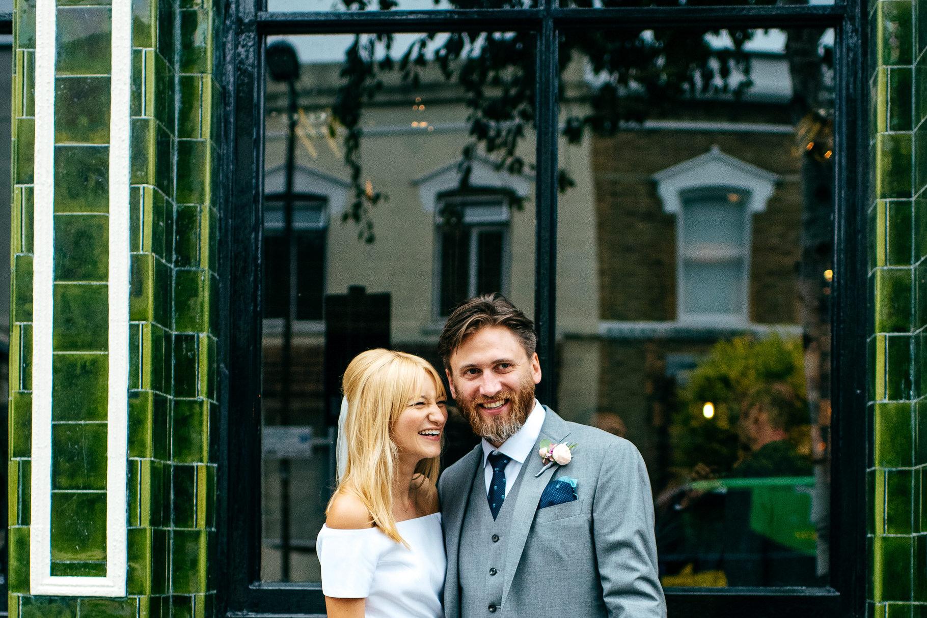 Stylish couple laughing outside Prince Albert Pub Camden