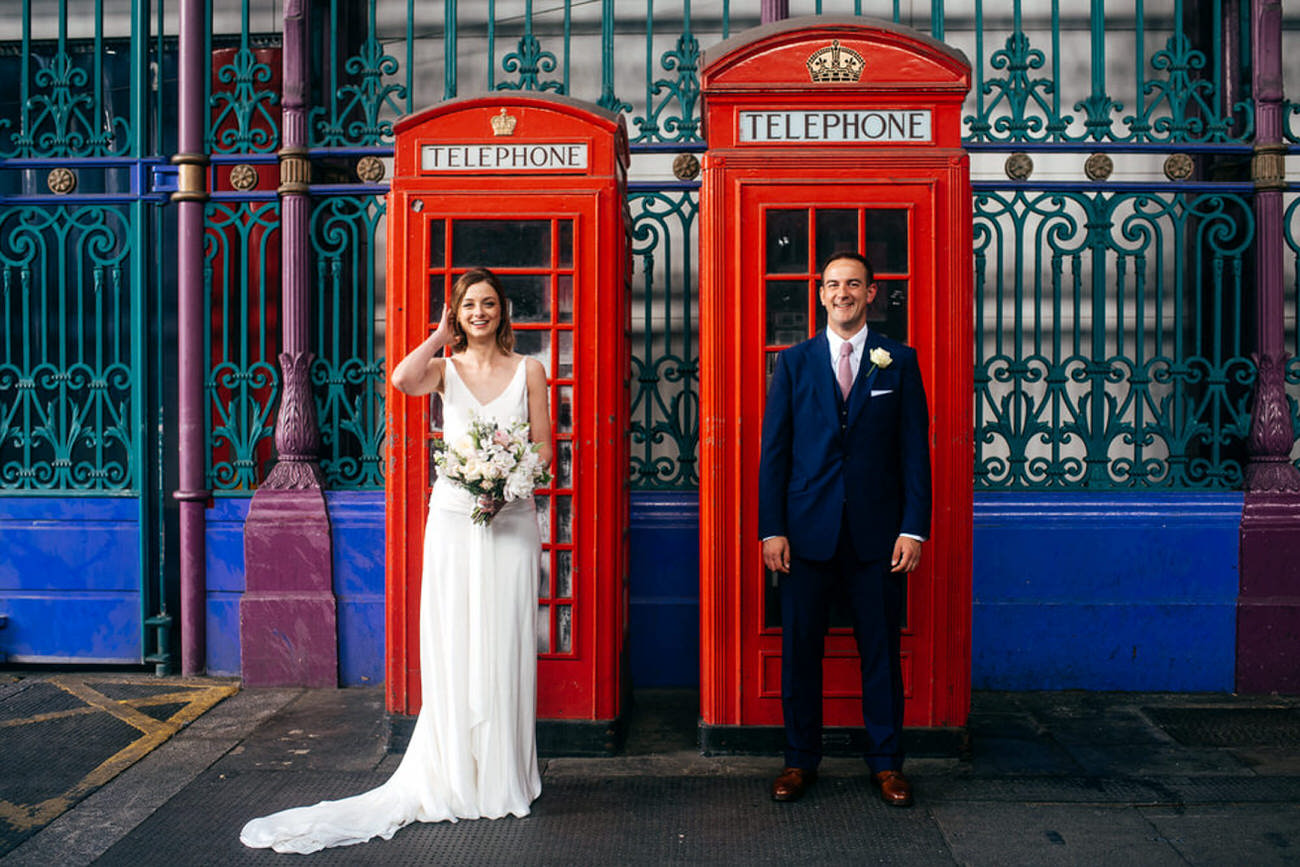 Bride and Groom in Smithfields Market standing by two phone boxes - Delphine Manivet dress
