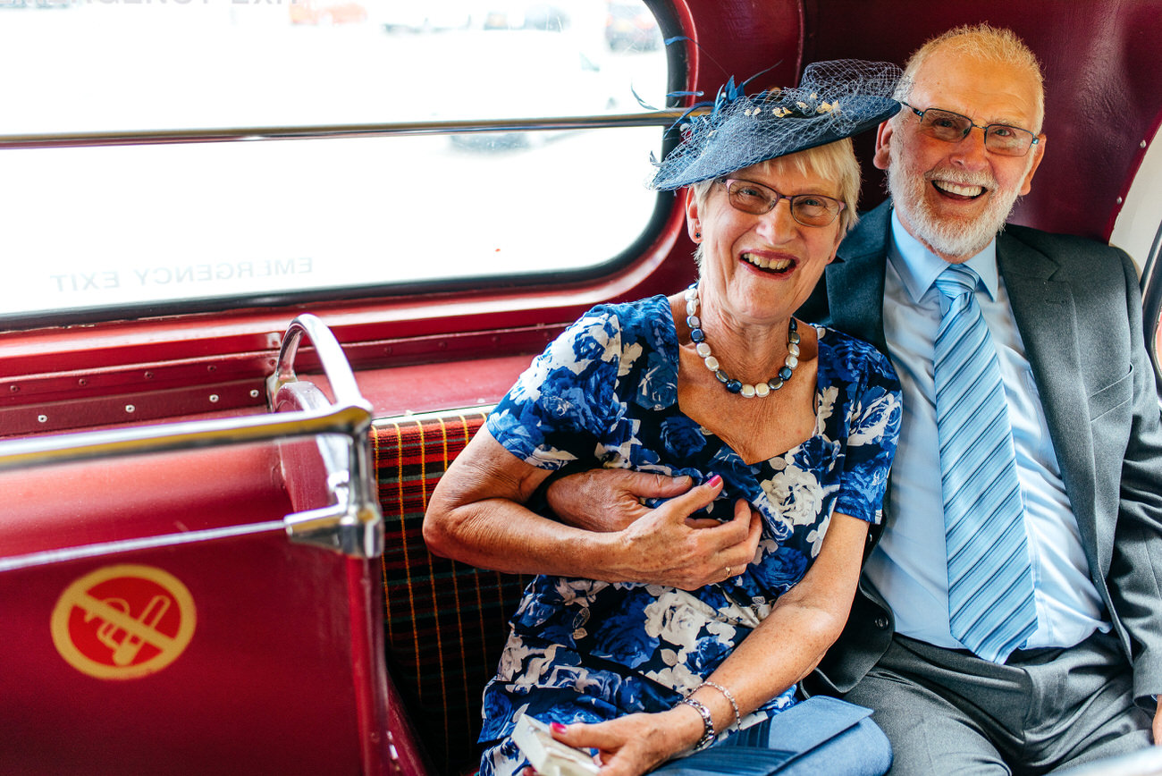 Older couple on the back of a London bus - man cheekily squeezing his wifes boob