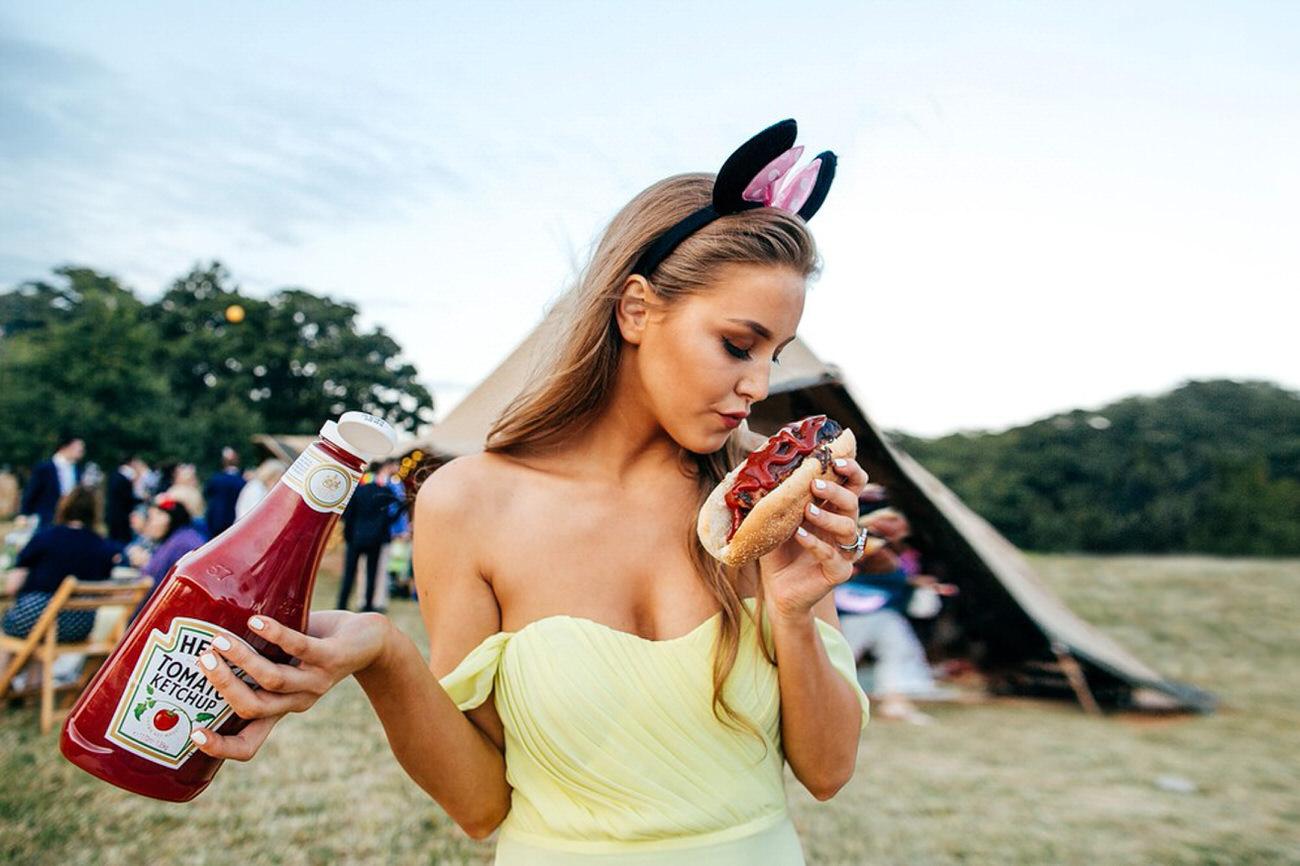 bridesmaid tucks into hotdog with a funny pout