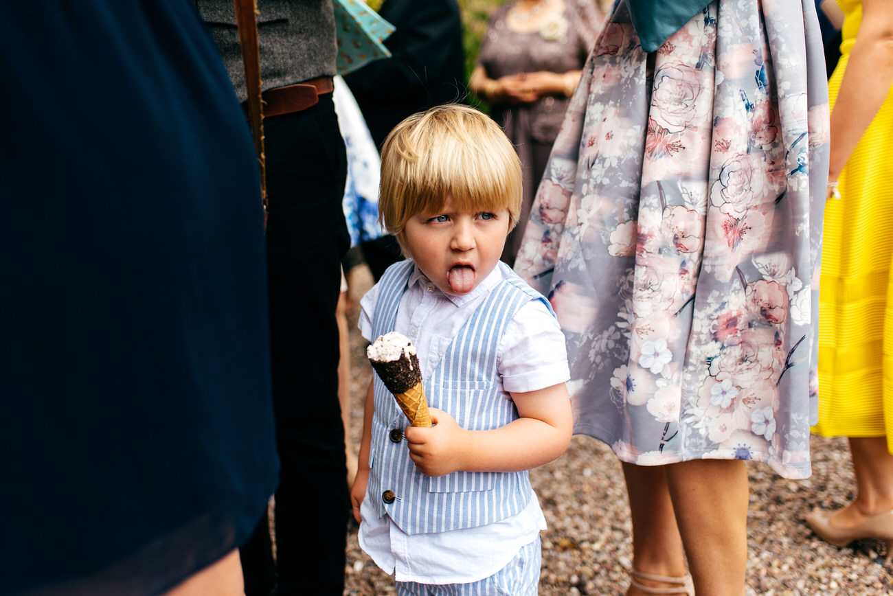 Boy with tongue out and ice cream in his hand on a hot summers wedding day