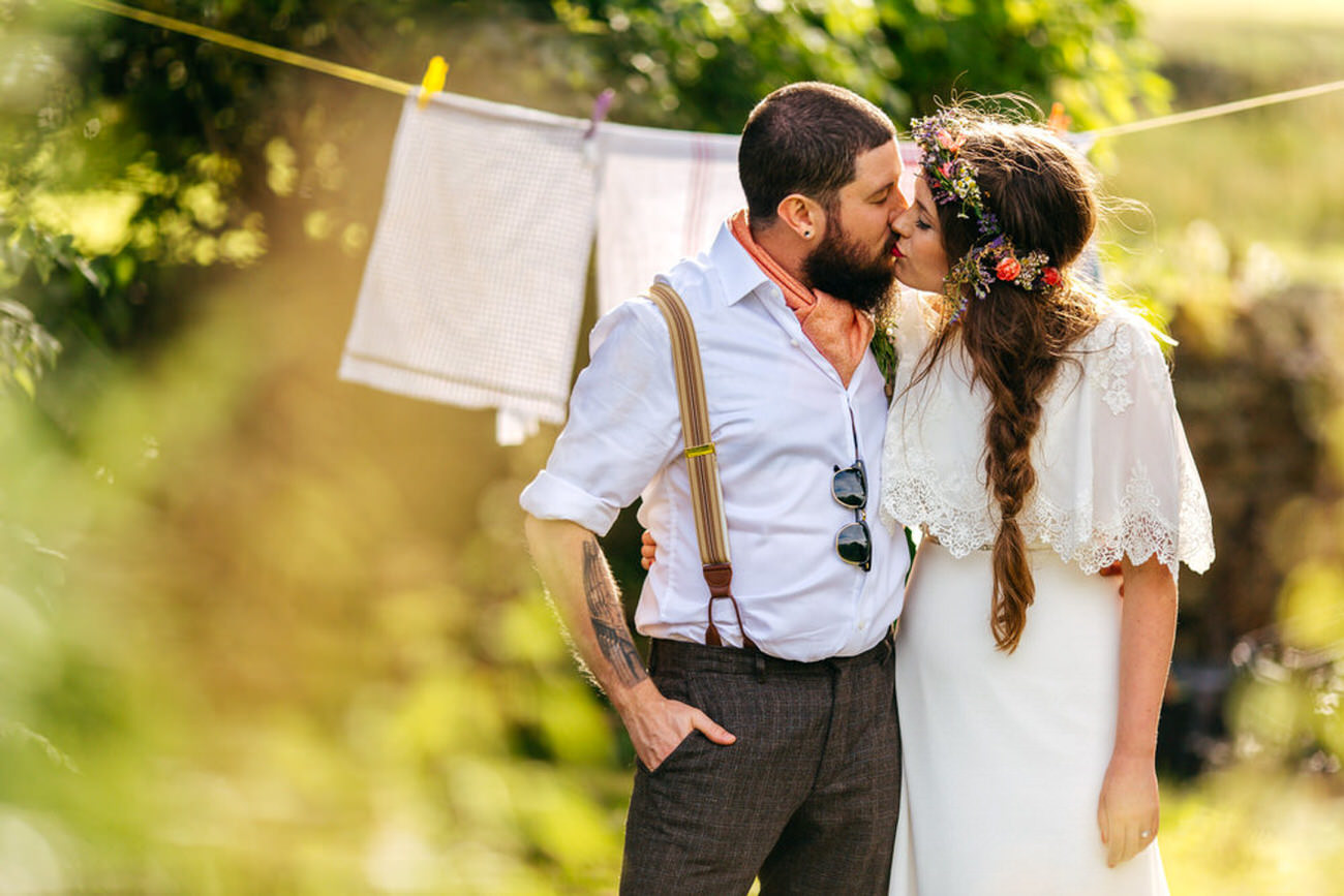 Couple in boho outfits have a kiss by a washing line at Chilli Barn Otley