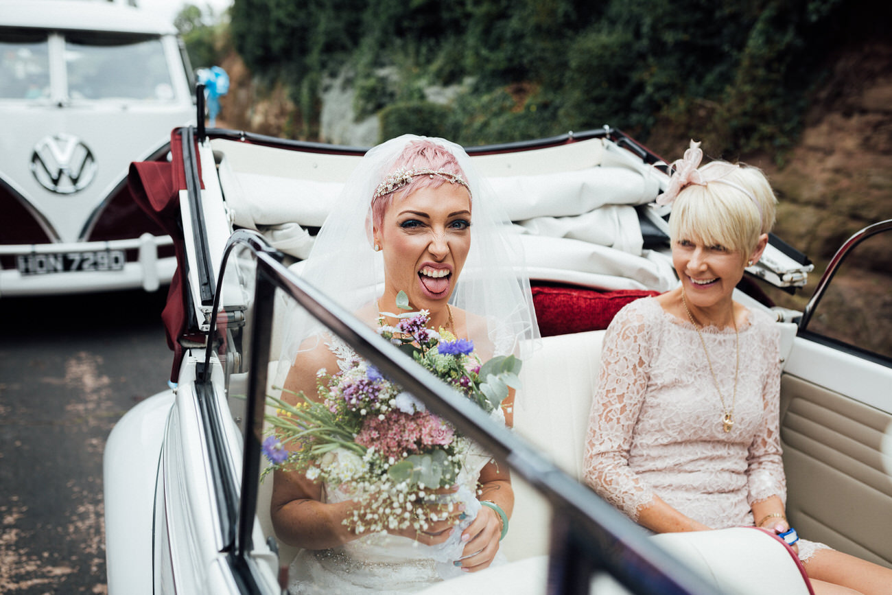 Pink haired bride in VW Beetle sticking her tongue out with mum laughing