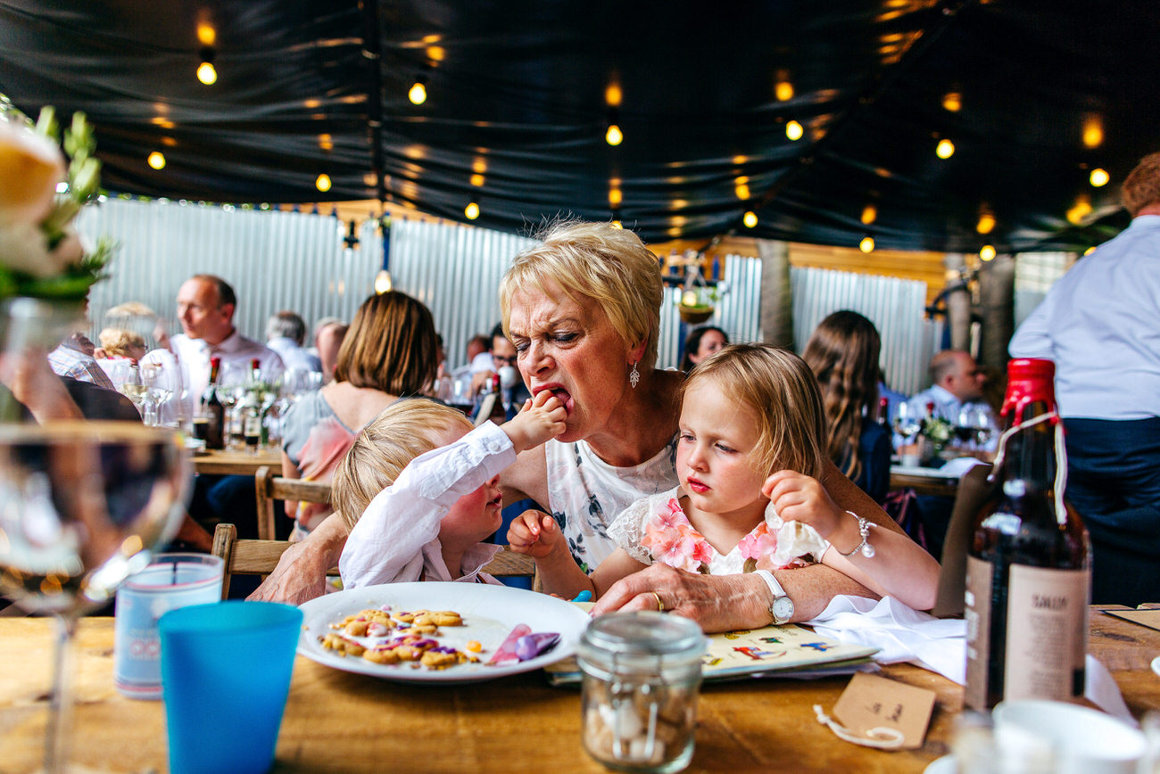 Twins shove sweeties in their nans mouth at a wedding at Brick Brewery Peckham