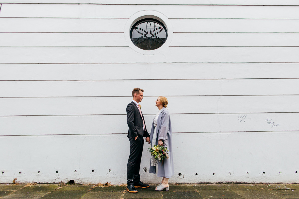 The Easton Pub Wedding London Wedding Photographer couple standing by wall with round window
