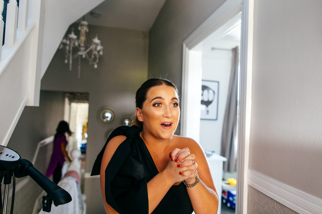 bridesmaids gushes over bride getting in to her Caroline Castigliano gown
