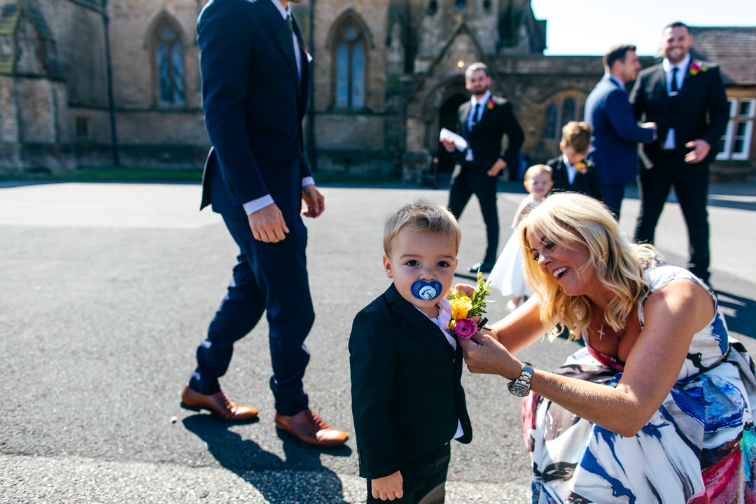 Pageboy gets buttonhole put on outside Rossall School church ceremony