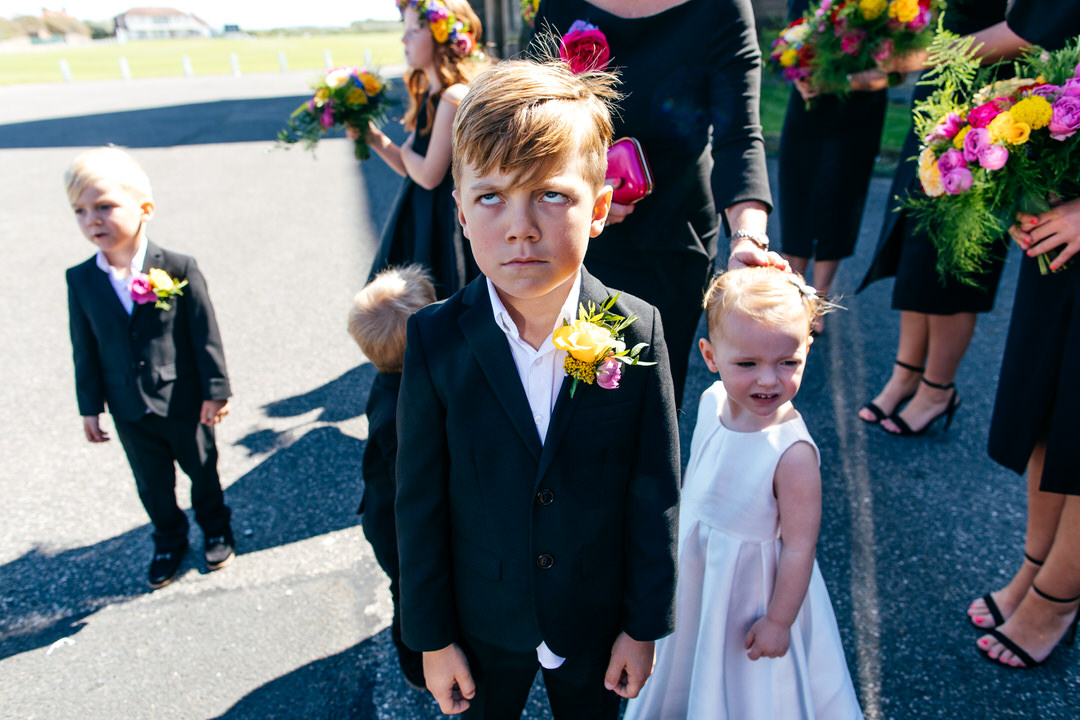 Funny image of pageboy rolling his eyes at wedding chaos outside Rossall School ceremony in Thornton Cleveleys