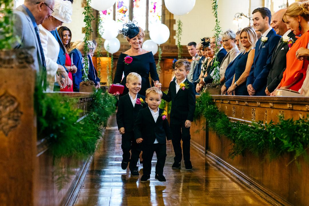 Rossall School wedding three pageboys walk up the aisle - black tie