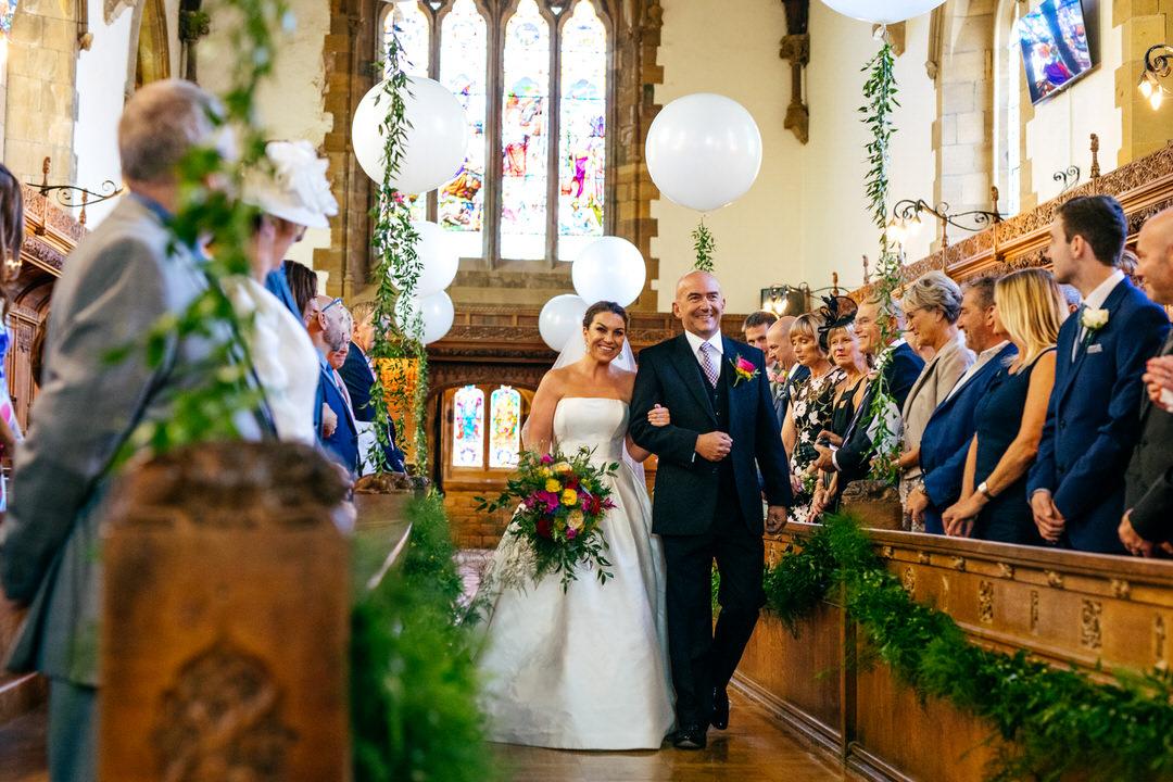Bride entrance on dad's arm at Rossall School Wedding Caroline Castigliano Gown