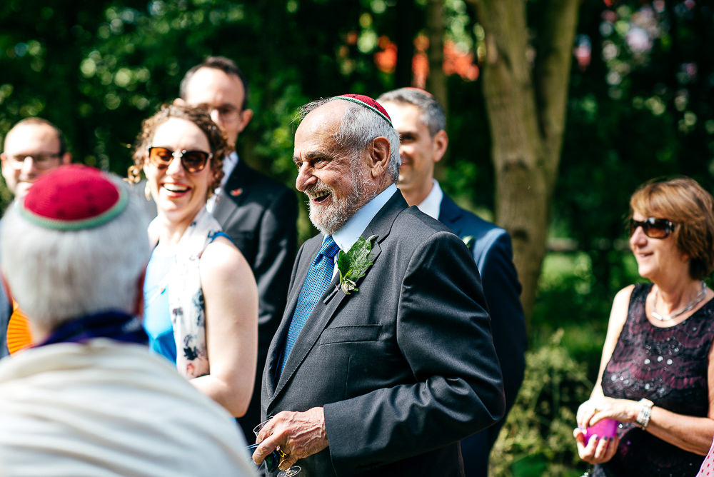 older-guest-wearing-watermelon-kippot-laughing-london-wedding-photographer