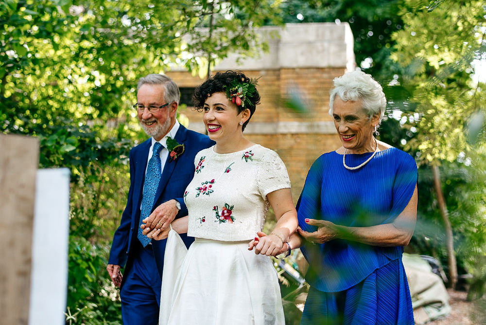 bride-walking-with-parents-surrounded-by-trees-woodberry-wetlands-wedding