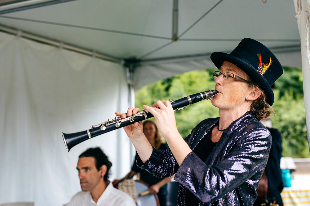 lady-wearing-top-hat-plays-clarinet-wearing-sequinned-jacket-london-wedding