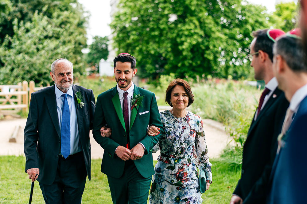groom-enters-with-parents-paul-smith-suit-jewish-wedding