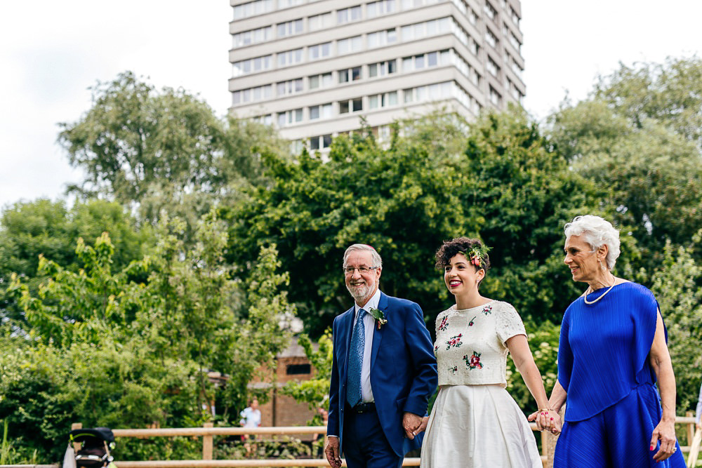 bride-stands-with-parents-woodberry-wetlands-wedding