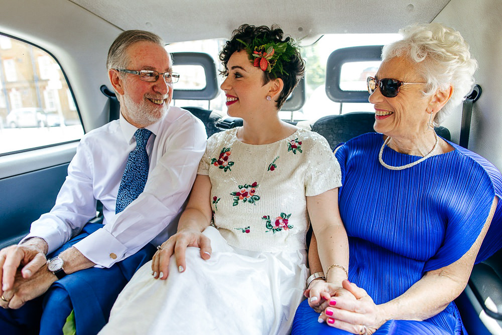 bride-sitting-with-parents-back-of-black-cab-london-wedding-photographer