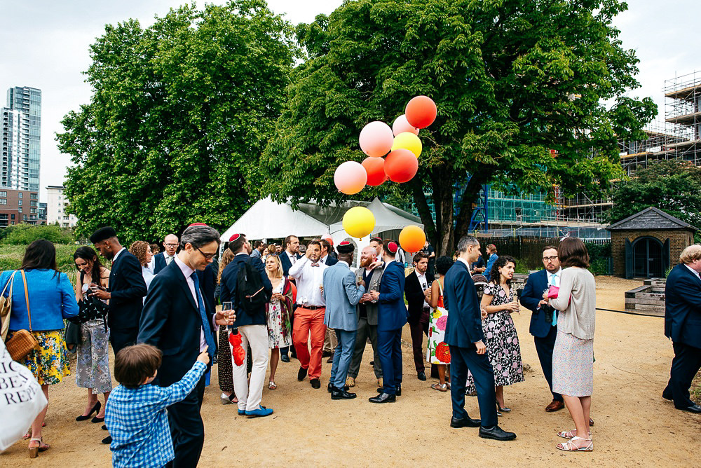 guests-mingle-under-trees-with-colourful-balloons