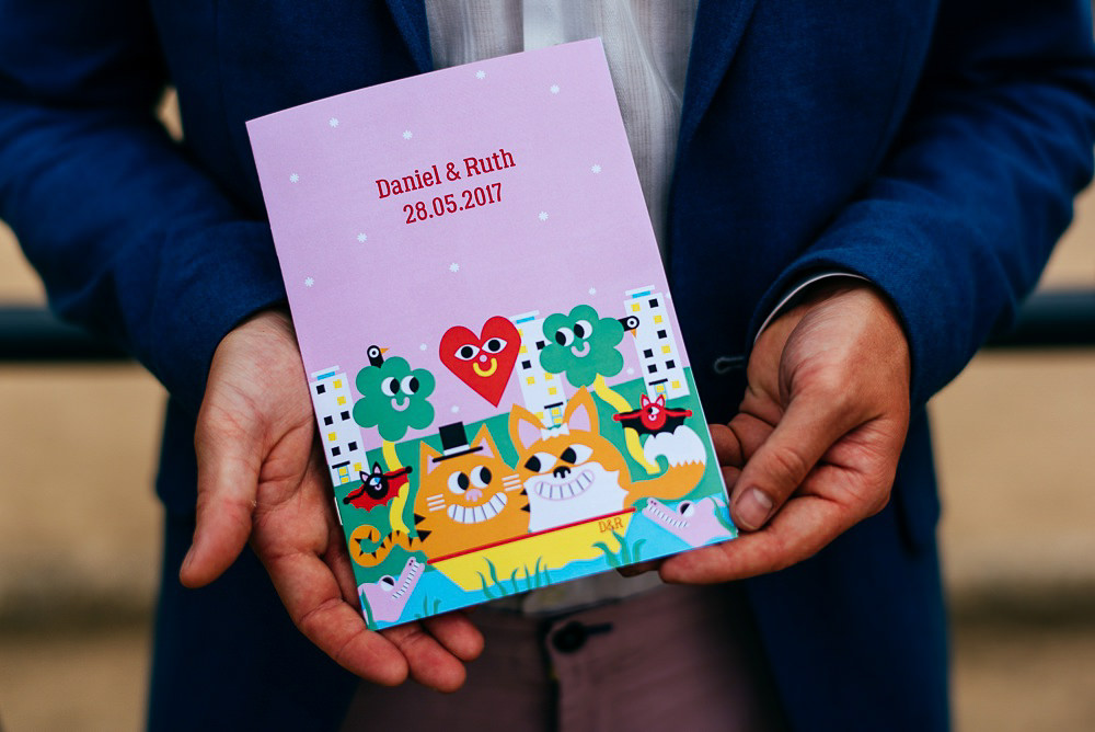 groom-holds-colourful-wedding-invitation-creative-wedding-photographer