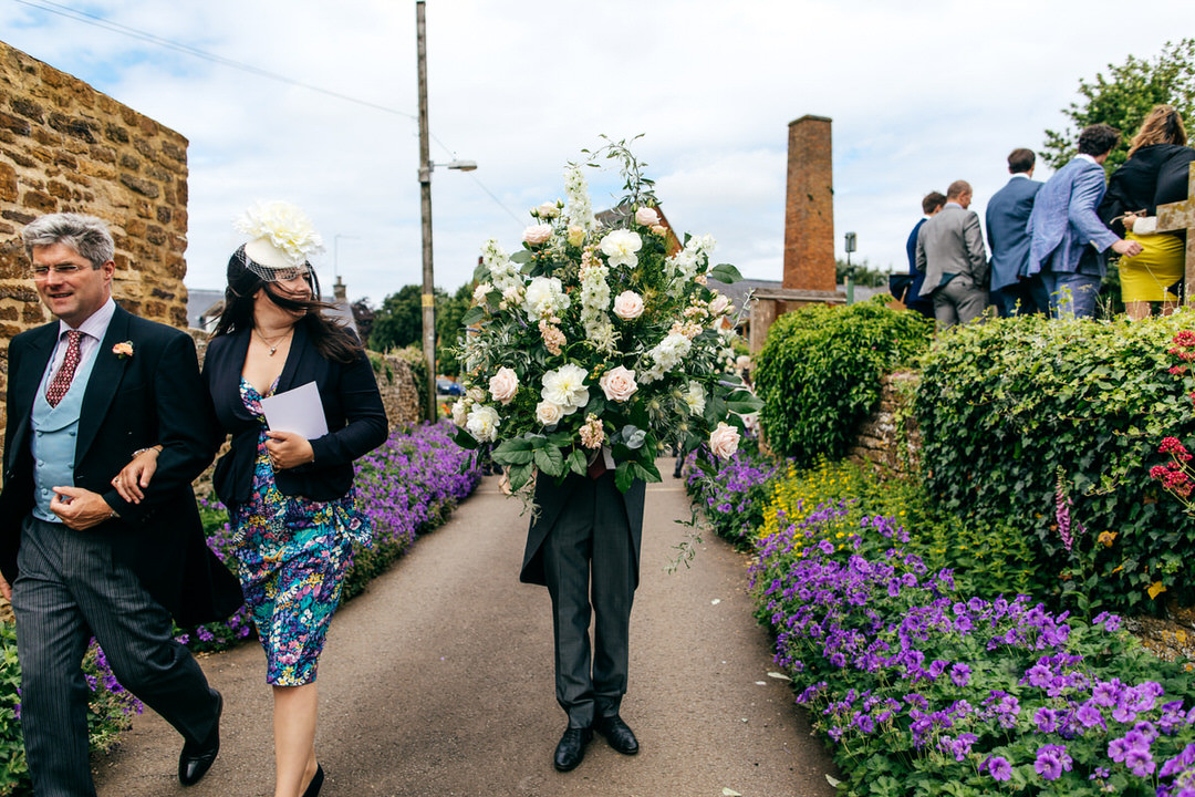 Grooms man holds massive urn of flowers and looks like some kind of flowery super hero at Farm Wedding at home