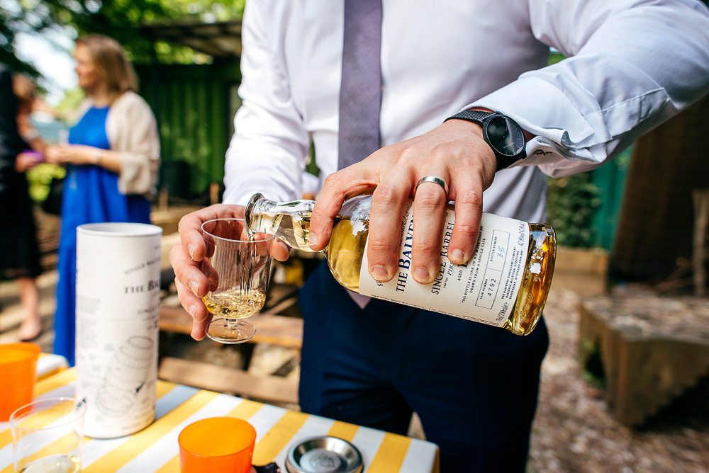 wedding-guest-pours-whiskey-woodberry-wetlands-wedding