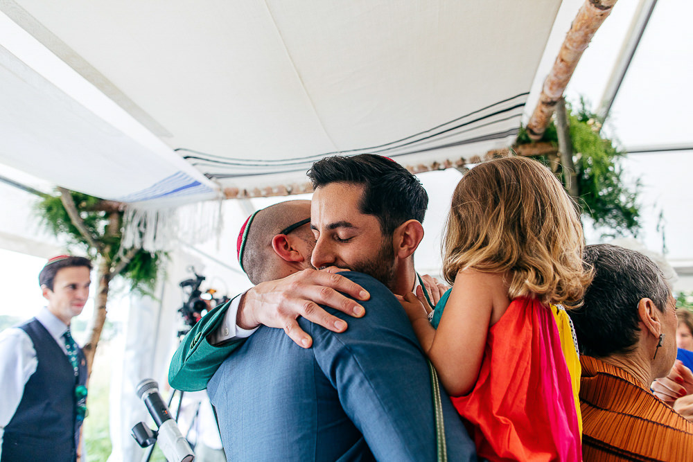 groom-embraces-guest-under-chuppah-jewish-wedding