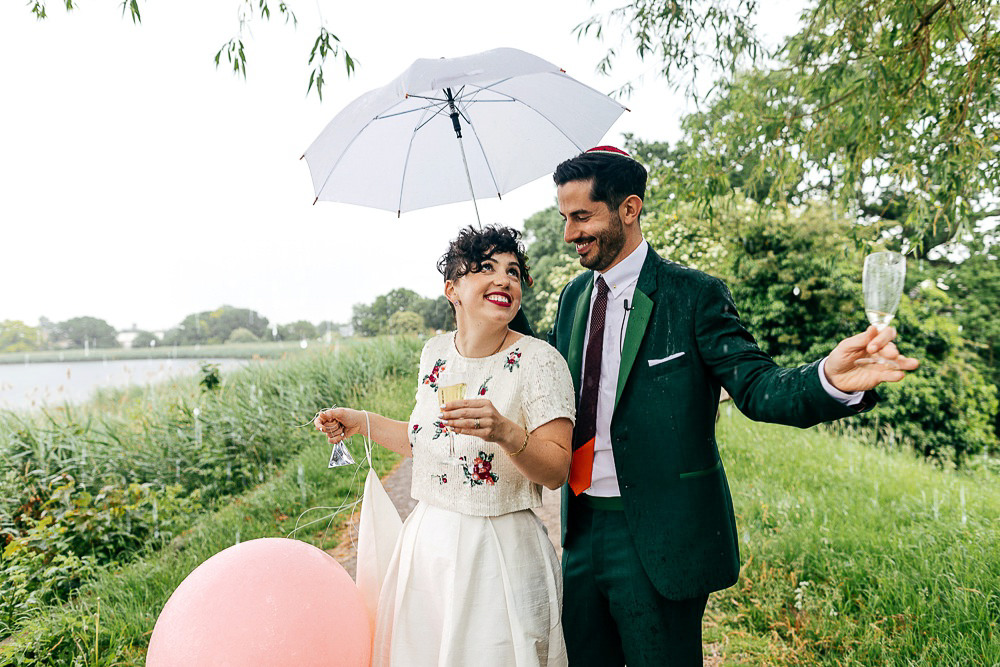 wedding-couple-drinking-champagne-under-umbrella