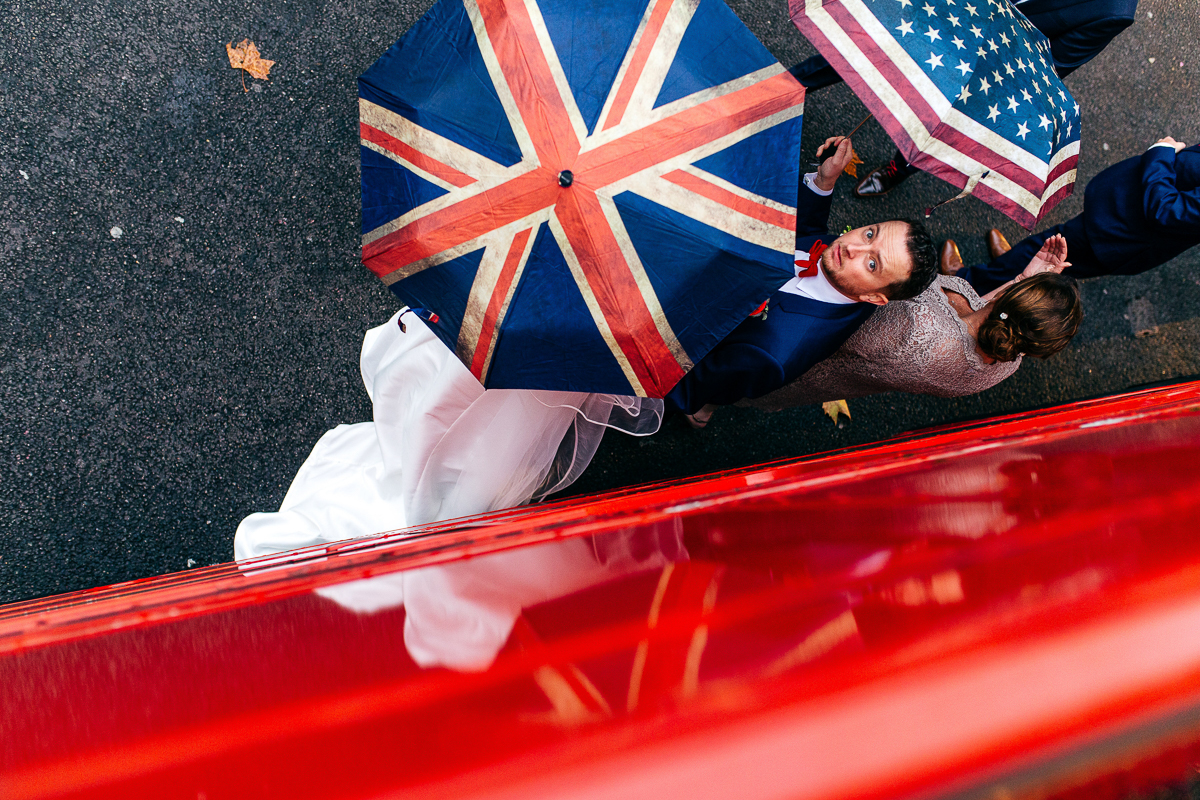 groom-standing-under-union-jack-umbrella-red-bus-london-wedding-photographer