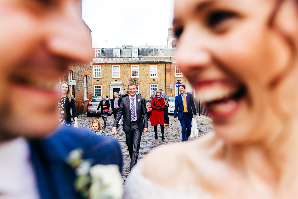guests-walking-down-cobbled-street-colourful-wedding