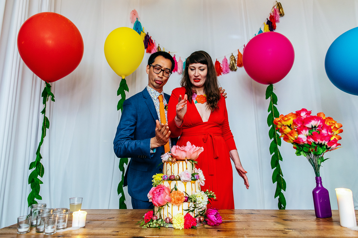 super-colourful-couple-prepare-for-cake-cutting-multi-coloured-balloons-jordanna-marston-photography