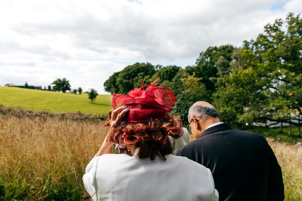 guests-walk-across-windy-field-holding-hats-creative-wedding-photographer