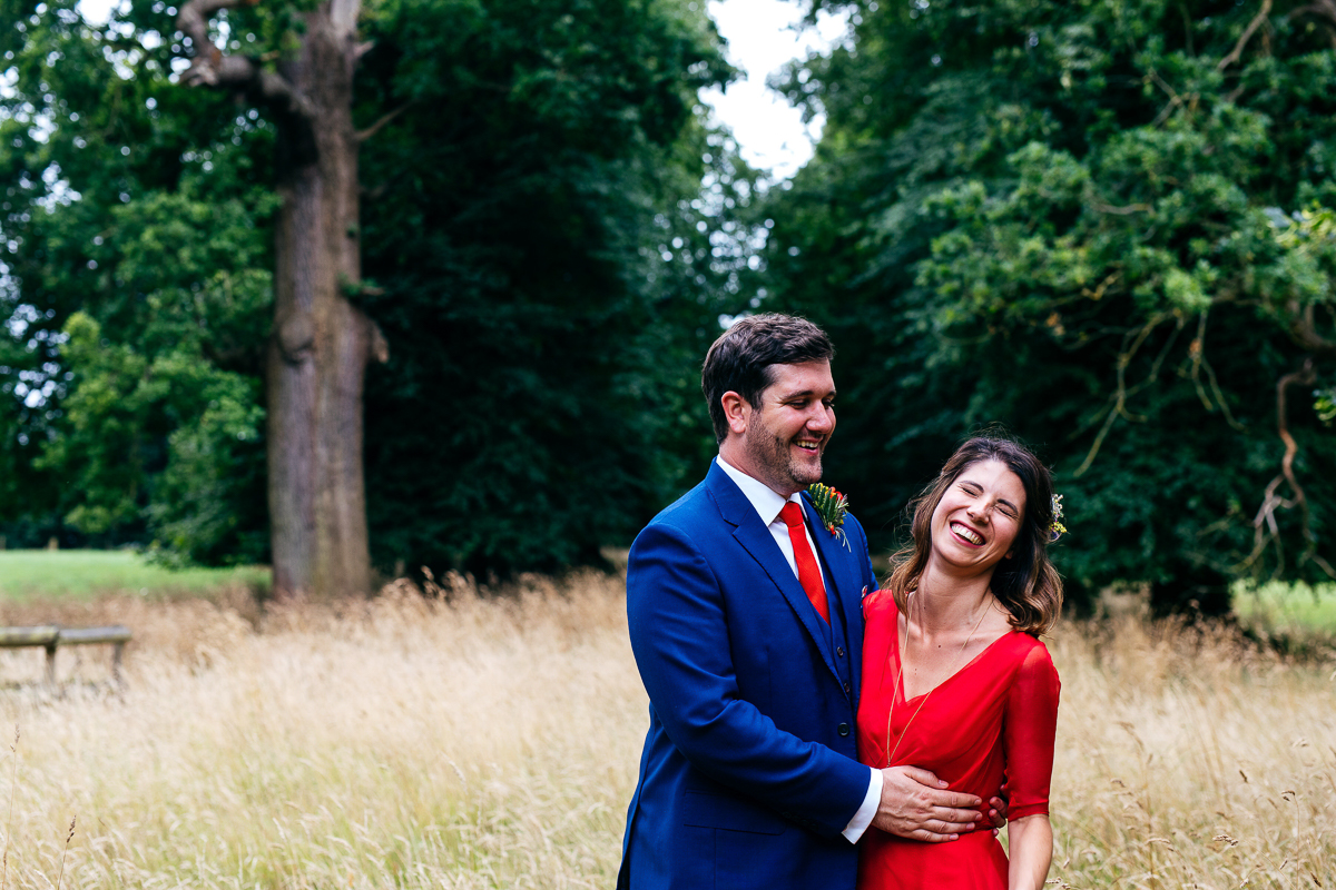 bride-wearing-red-wedding-gown-held-by-groom-wearing-cobalt-blue-suit