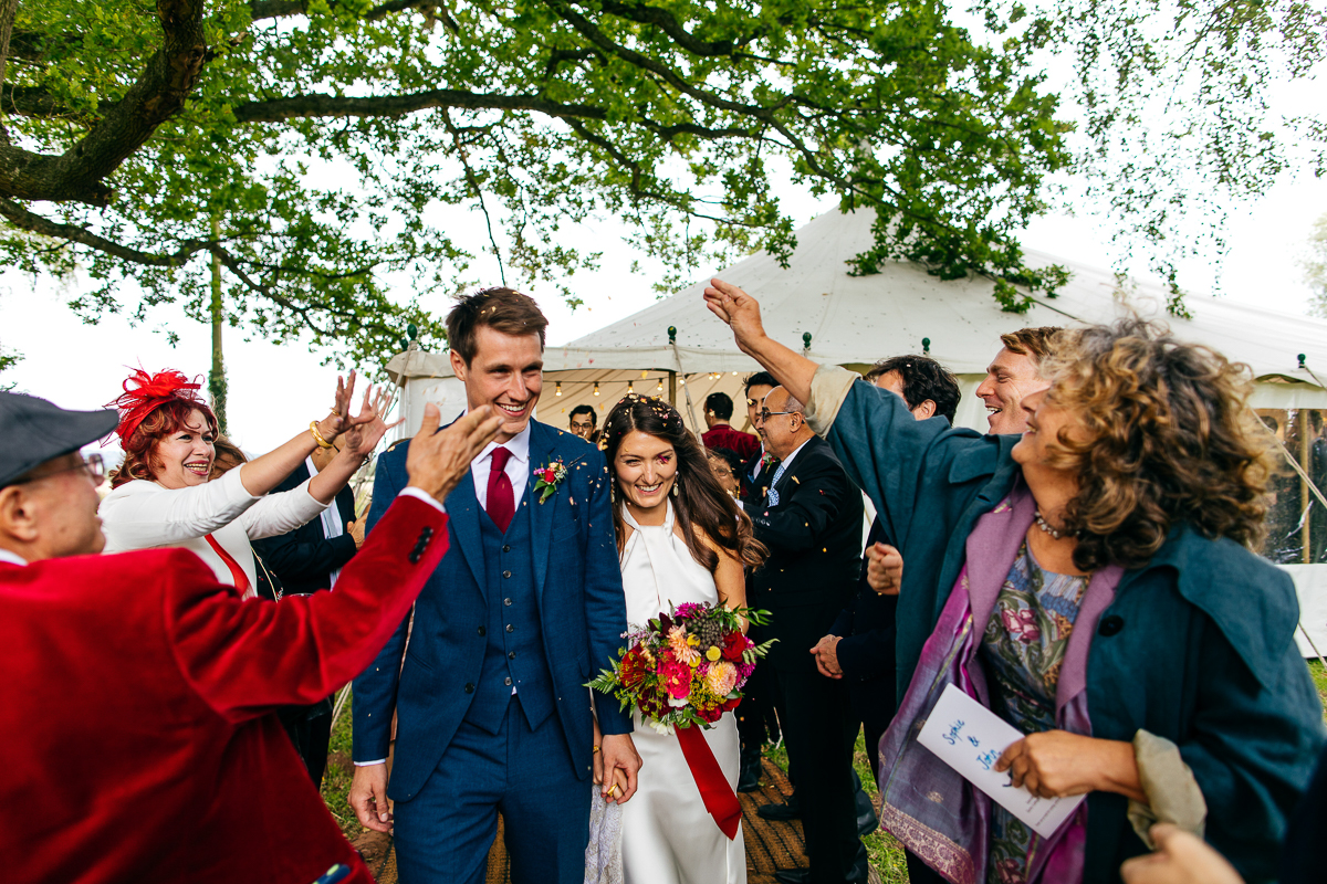 bride-holding-wildflower-bouquet-showered-with-confetti-london-wedding-photographer