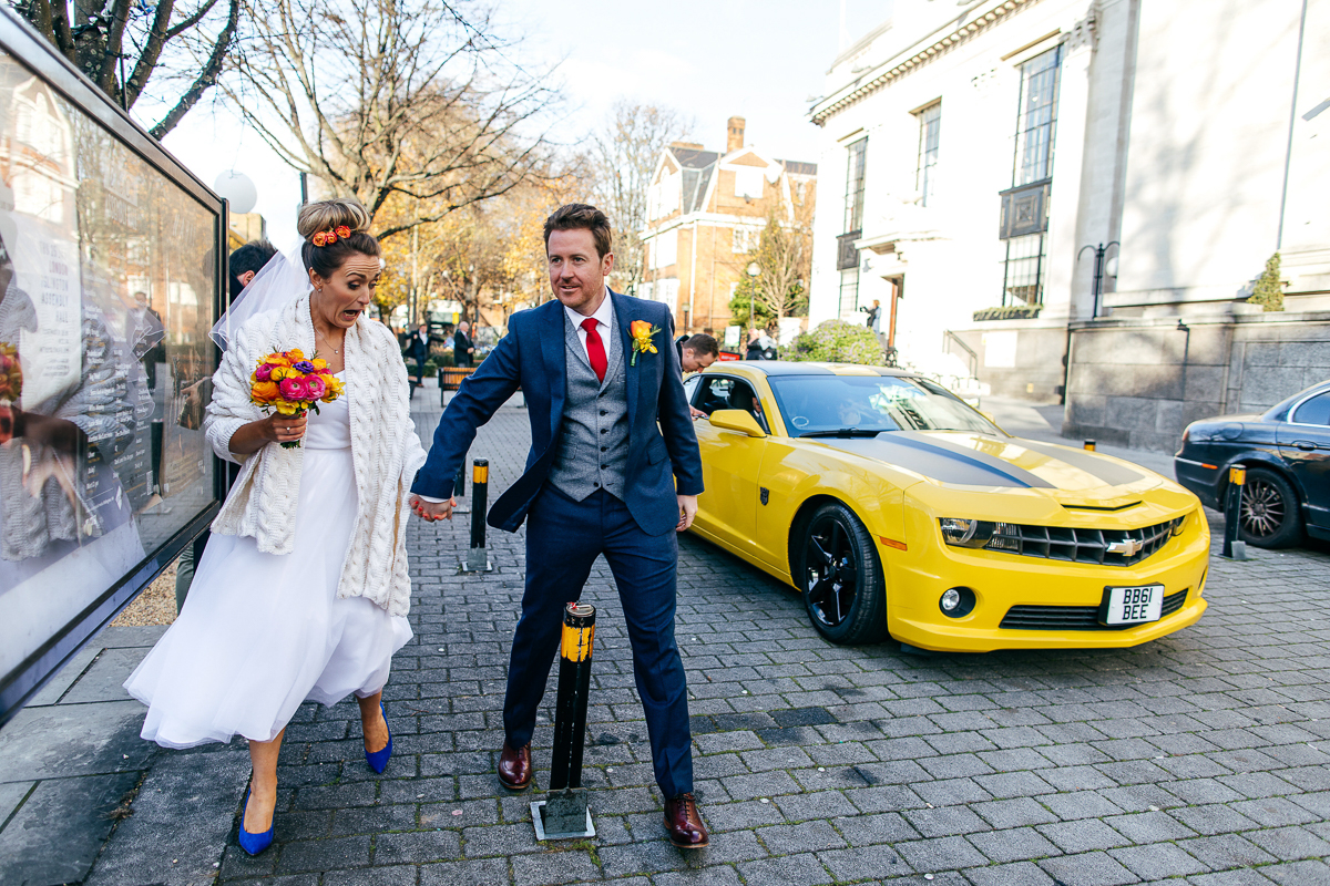 funky-bride-wearing-blue-shoes-walking-with-groom-past-yellow-car-london-wedding-photographer