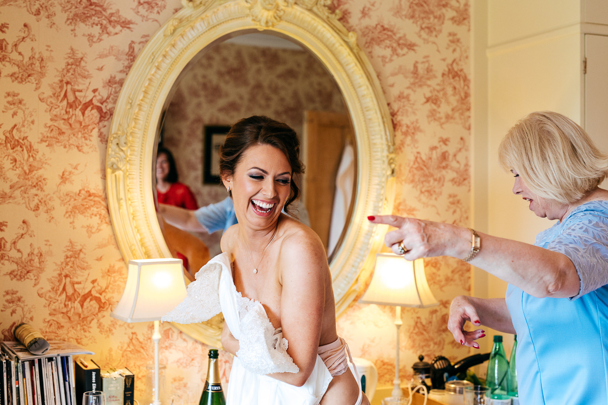 laughing-bride-gets-ready-with-mum-lace-wedding-dress-creative-wedding-photographer