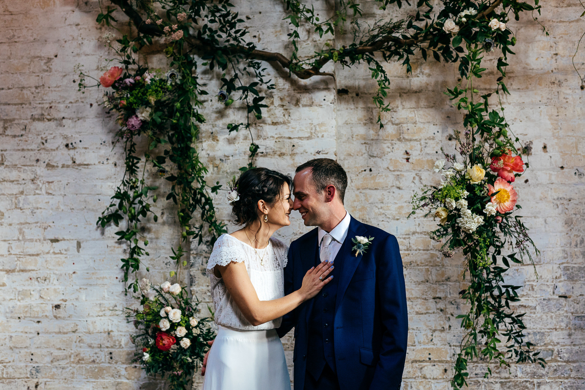 couples-portrait-under-flower-arch-against-white-brick-wall-jordanna-marston-wedding-photographer
