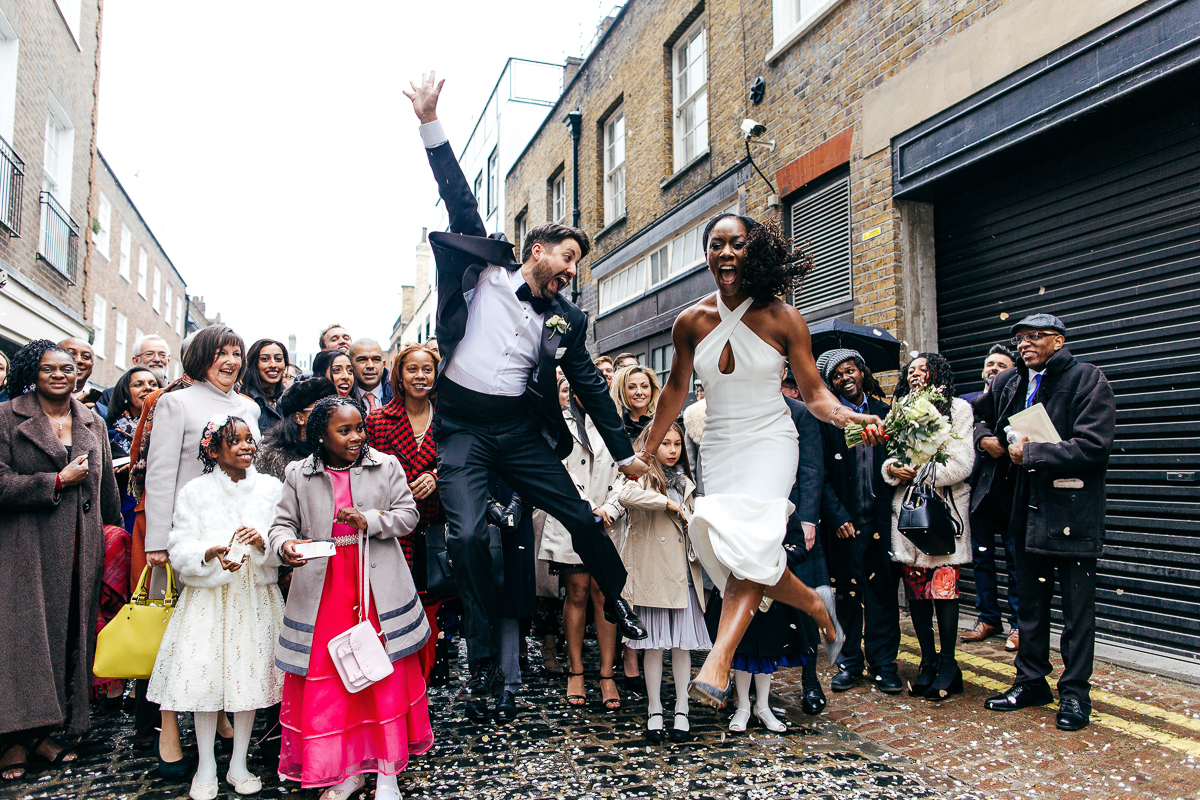 urban-bride-jumping-wearing-halterneck-dress-with-groom-surrounded-by-guests