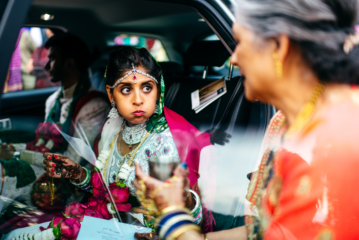 nervous-bride-waits-in-car-wearing-sari-has-sip-of-water-creative-wedding-photographer