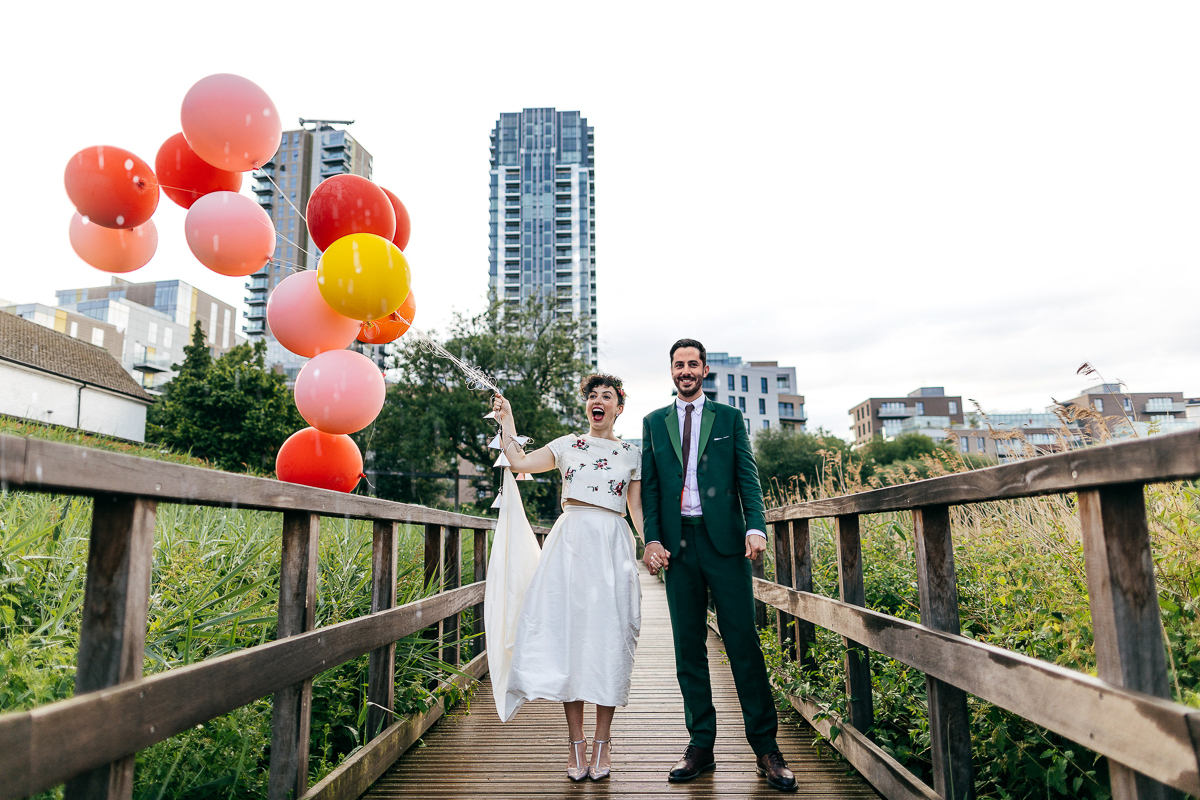 couple-stand-in-rain-holding-balloons-woodberry-wetlands-jewish-wedding-photographer