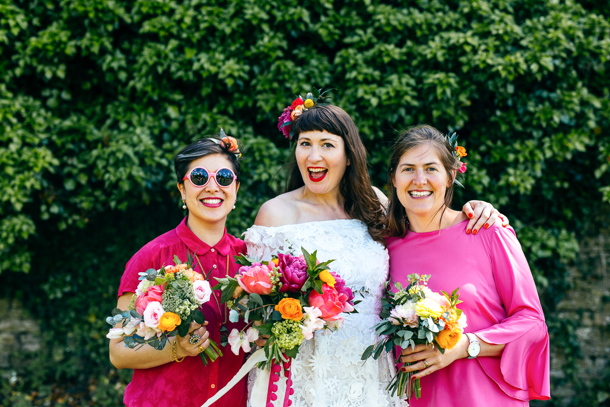 colourful-boho-bride-standing-with-bridesmaids-wearing-pink