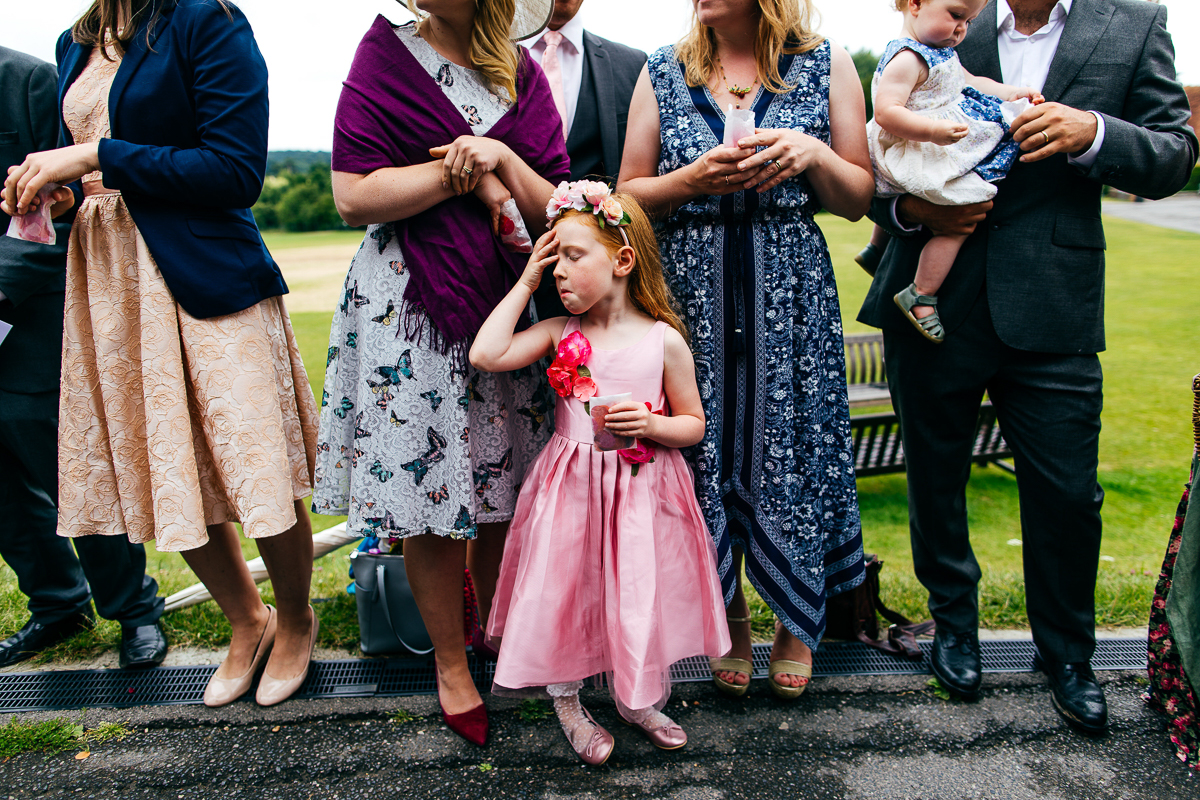 red-haired-flower-girl-pink-silk-dress-prepares-for-confetti-throw-london-wedding-photographer