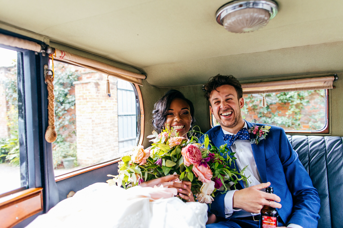 laughing-bride-and-groom-back-of-classic-car-creatuve-wedding-photographer