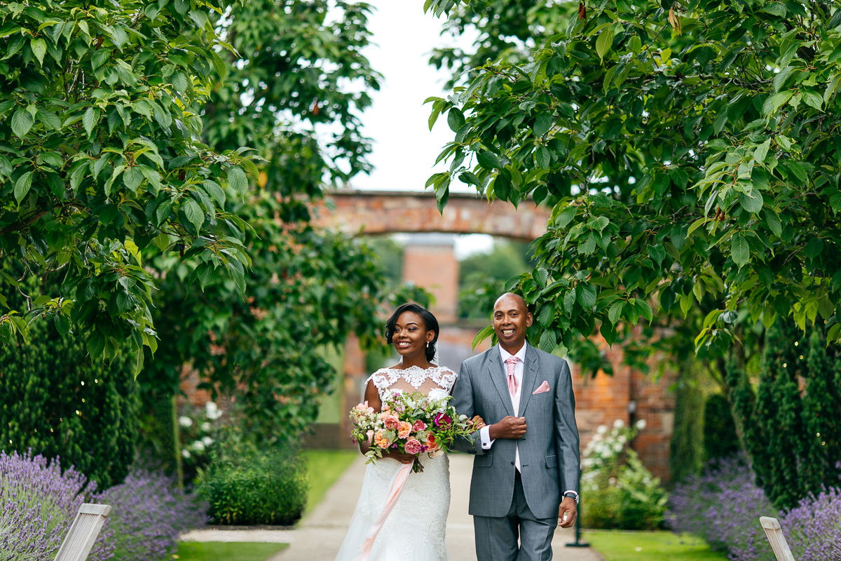 bride-walks-through-trees-to-ceremony-with-father-lace-wedding-dress