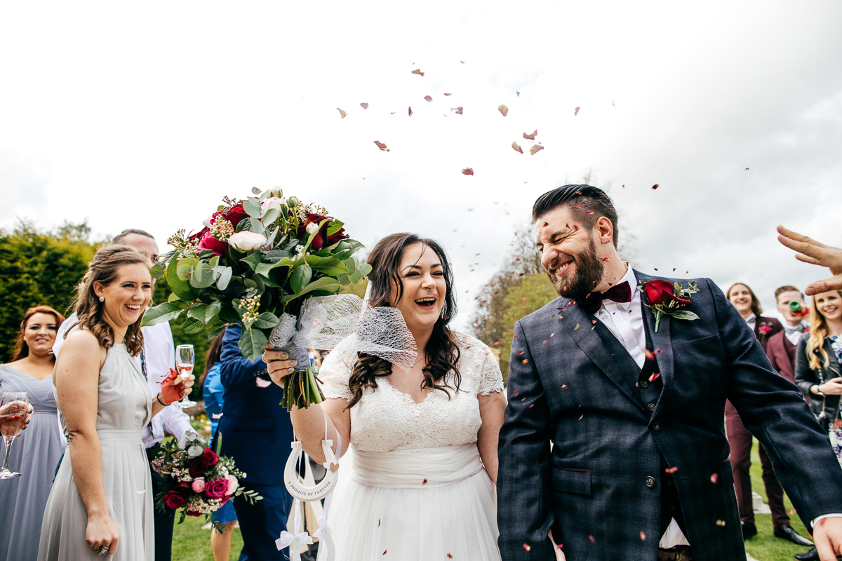 happy-couple-walk-through-confetti-tunnel-laughing-creative-london-wedding-photographer