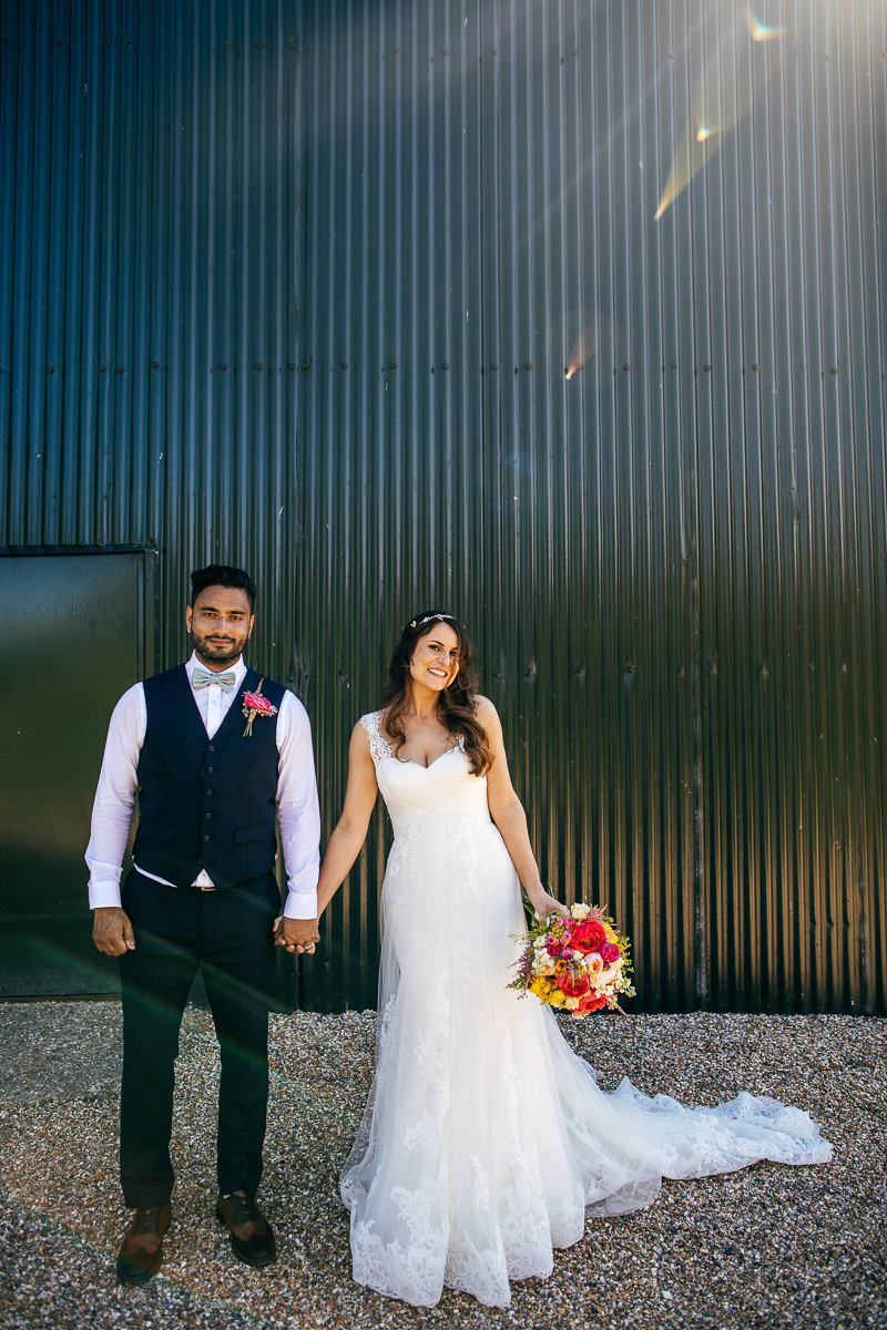 bride-and-groom-pose-in-front-of-barn-smiling-in-sun