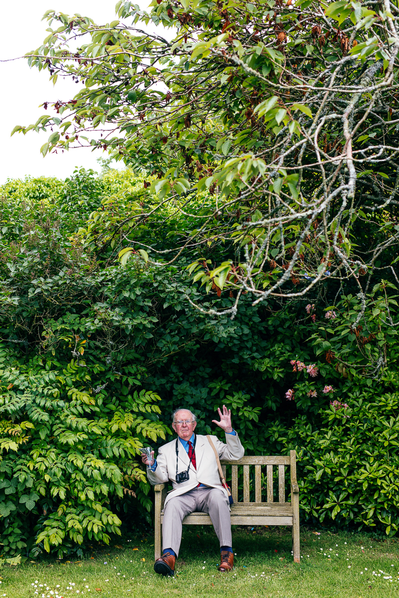 elderly-guest-sat-on-bench-waving-jordanna-marston-photography