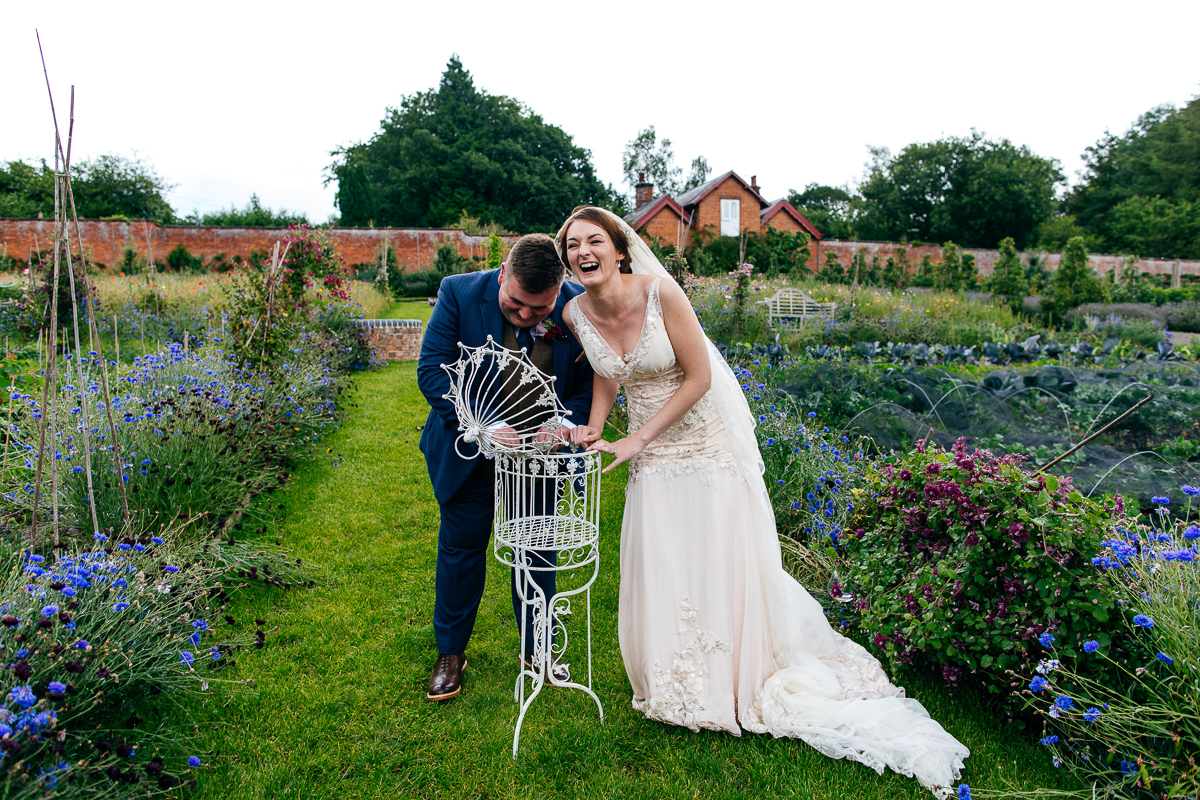 laughing-bride-and-groom-muck-about-in-gardens-london-wedding-photographer