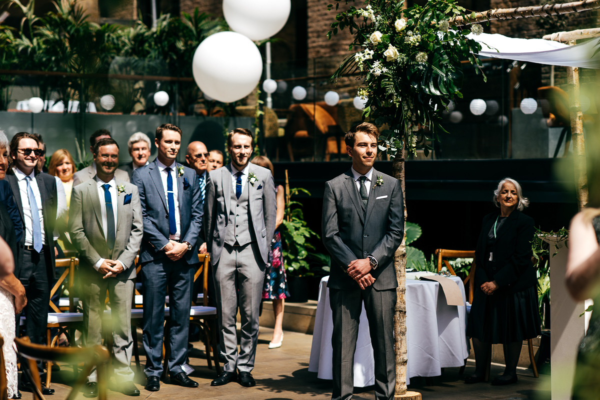 grooms-waits-in-sun-for-bride-creative-wedding-photographer
