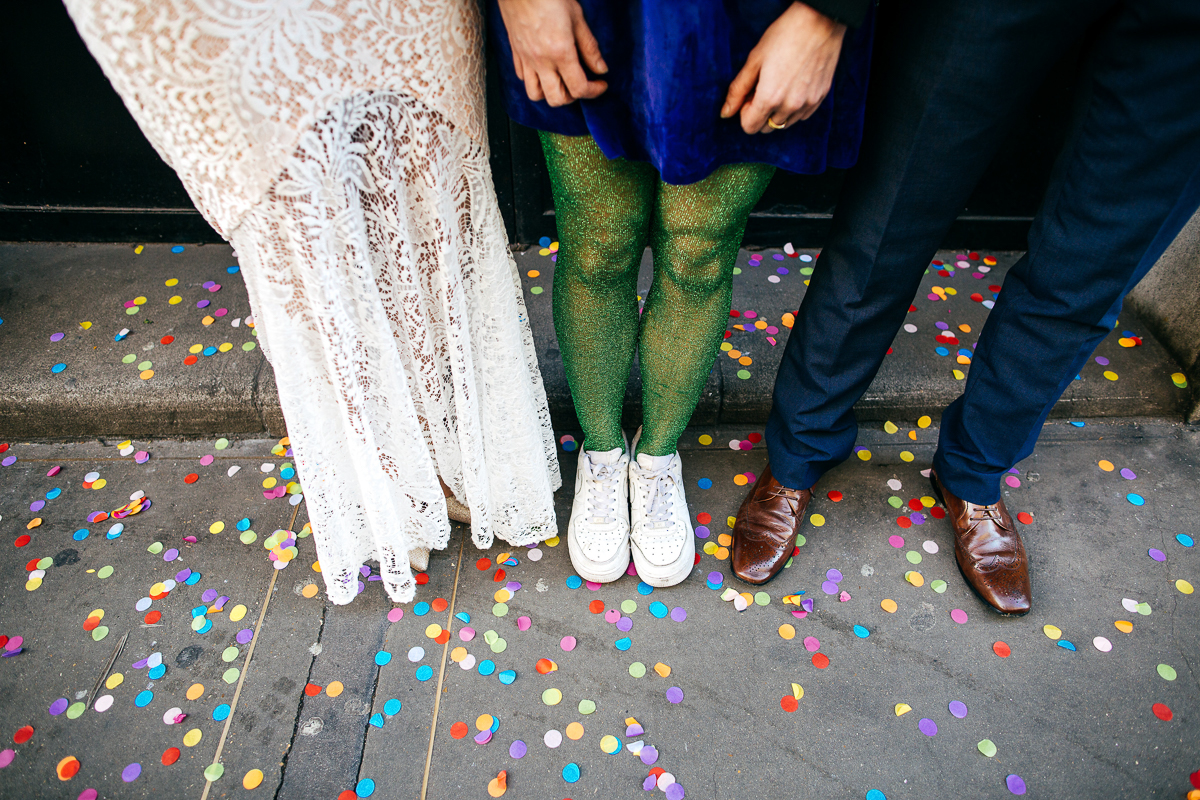 bride-groom-stand-either-side-of-guest-wearing-green-glittery-tights-amongst-confetti