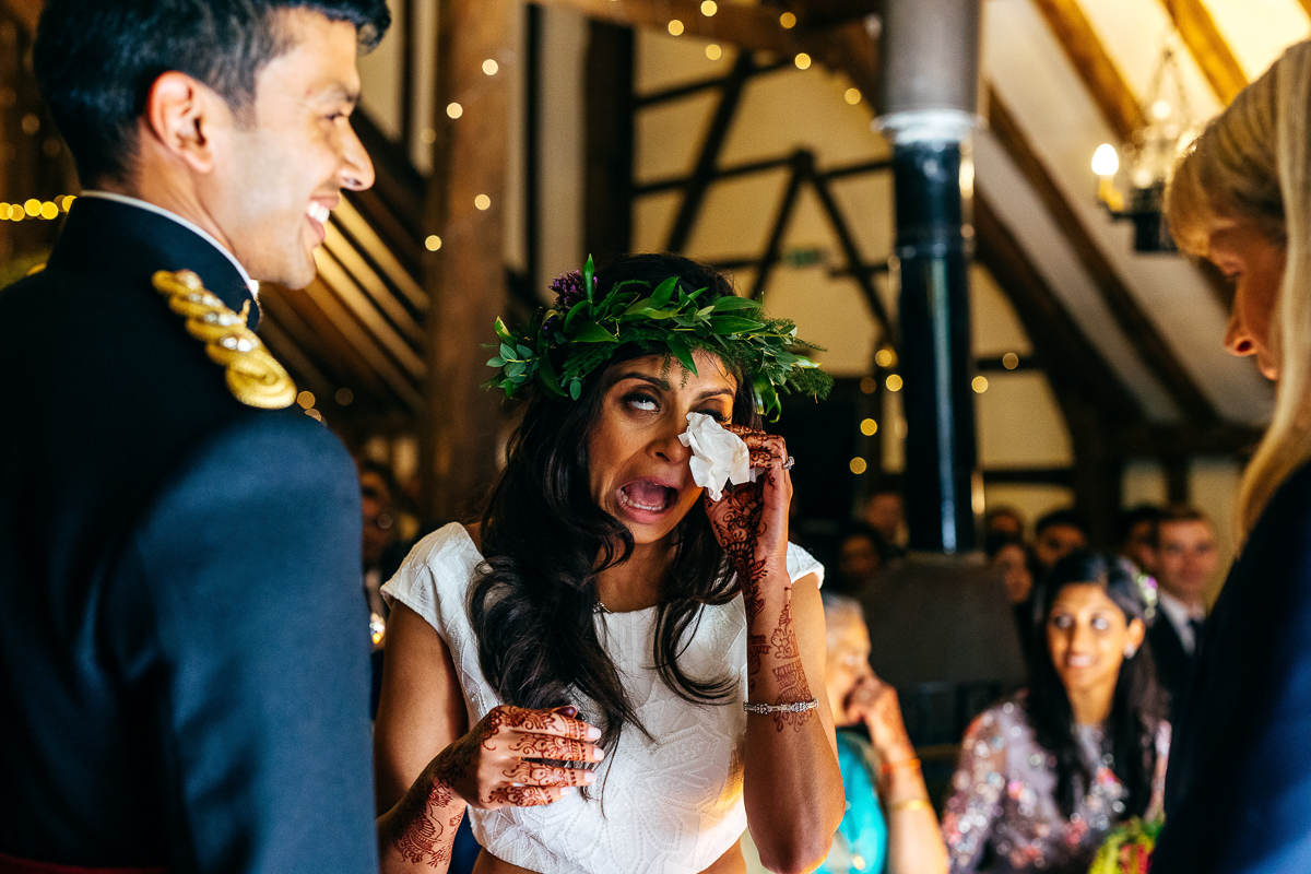 bride-wearing-floral-crown-wipes-away-tears-during-ceremony