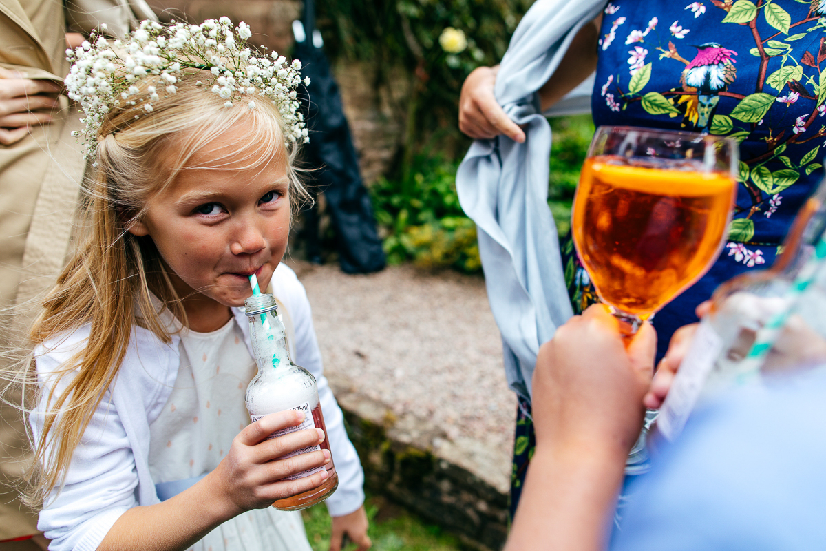 cheeky-flower-girl-with-flower-crown-drinks-fizzy-drink-smiling